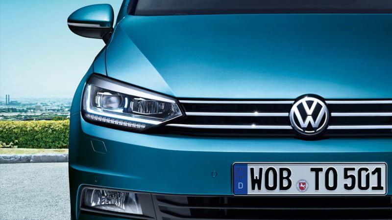 VW Touran vista da davanti con fari con luci diurne a LED in un parcheggio, sullo sfondo una zona industriale