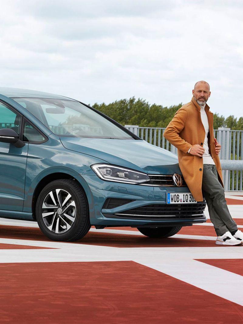 Un homme s'appuie contre le capot d'une Golf Sportsvan Last Edition.