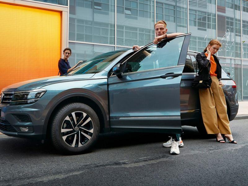 Twee vrouwen en één man staan rond de Tiguan Allspace IQ.DRIVE