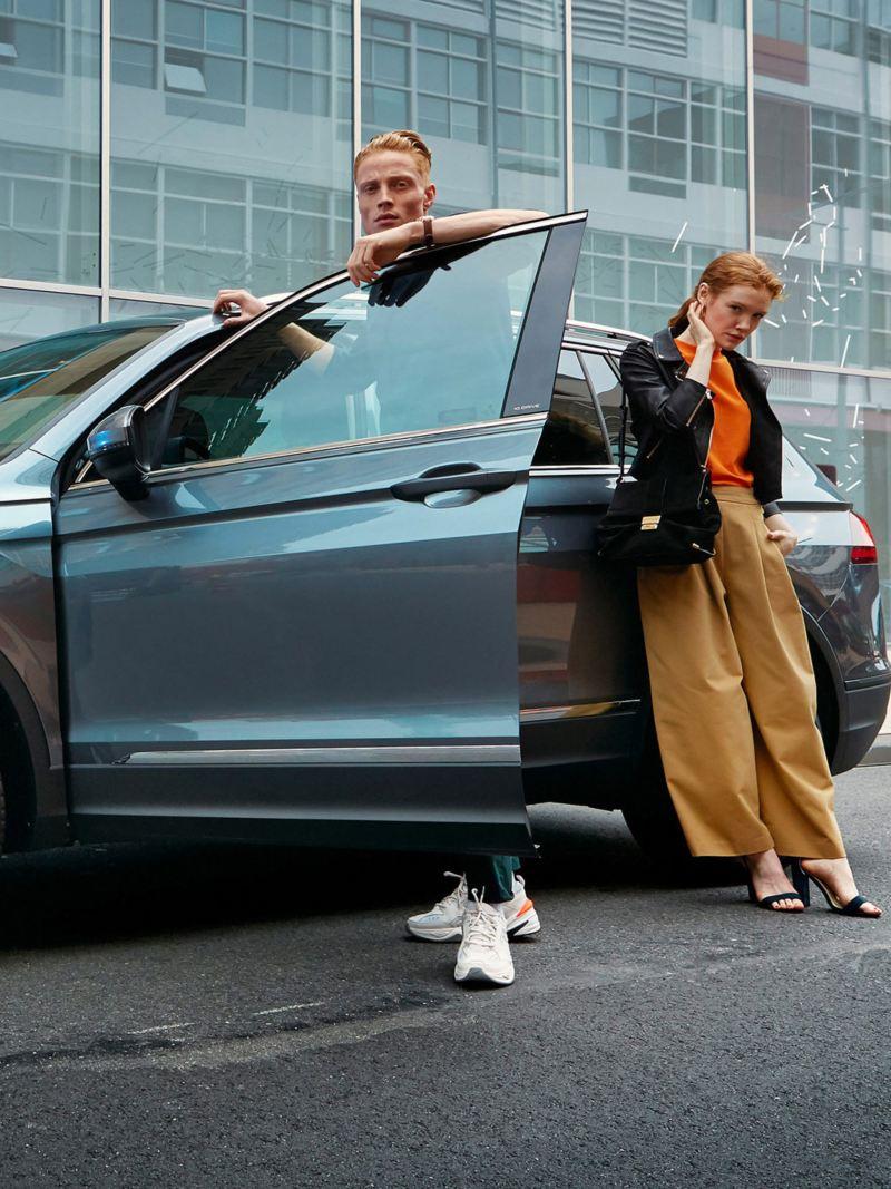 Dwie kobiety i mężczyzna stoją wokół Tiguana Allspace IQ.DRIVE