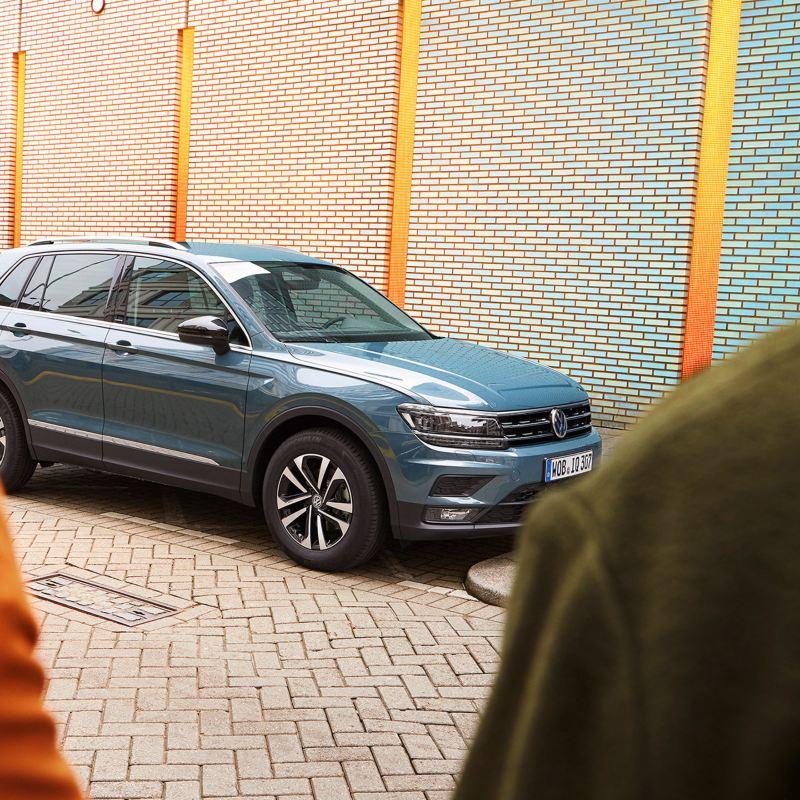 En Volkswagen Tiguan står parkerad på en gata. En kvinna och man syns i förgrunden.