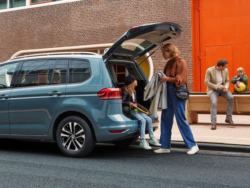 Matka i dziecko przed Touranem IQ.DRIVE z otwartym bagażnikiem