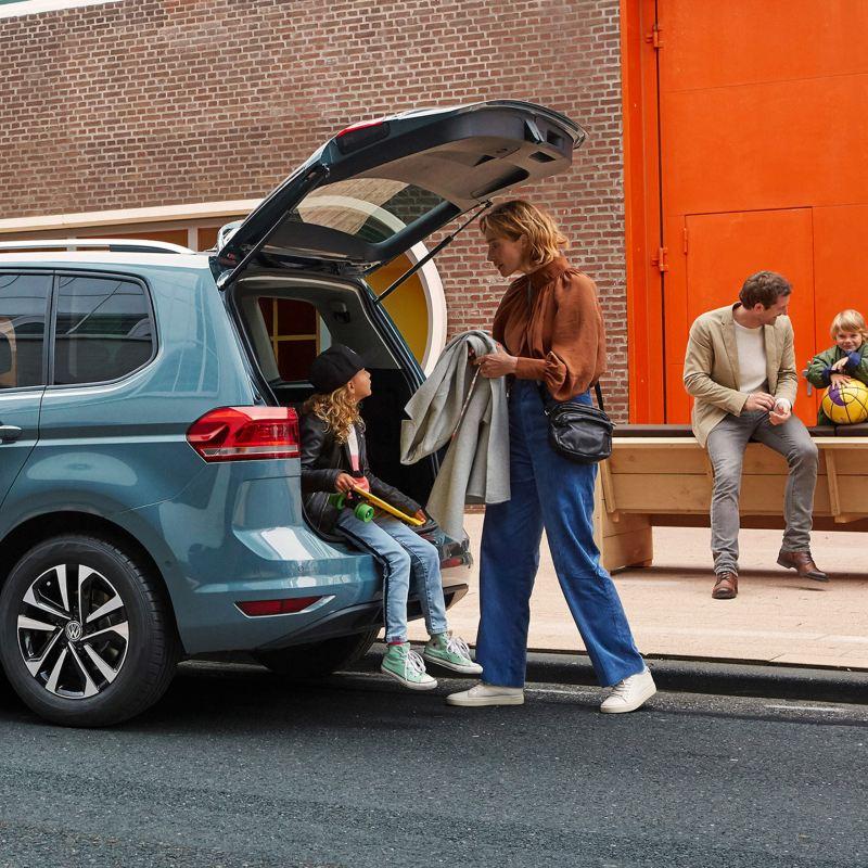 ragazza seduta sul bordo del bagagliaio aperto di VW Touran mentre la mamma le porge il cardigan