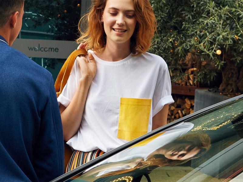 Ragazza con maglia bianca e tasca gialla sorride vicino ad una vettura Volkswagen