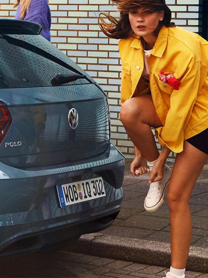 Vrouw achter de Polo IQ. DRIVE maakt haar schoenveter vast