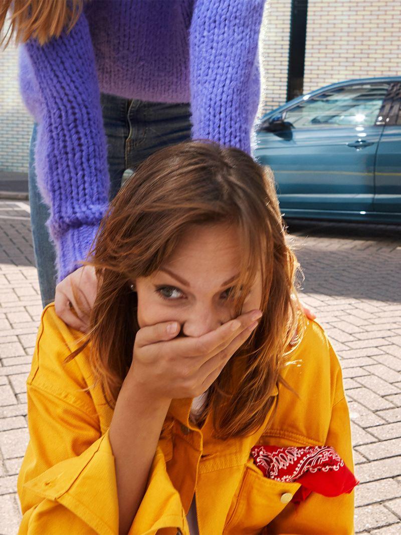 Twee vrouwen amuseren zich; op de achtergrond staat de Polo IQ.DRIVE