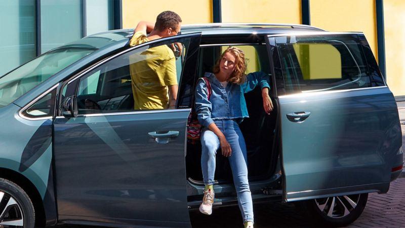 Un femme est assise dans un Sharan IQ.DRIVE ouvert, un homme se tient dans l'ouverture de la portière du conducteur.