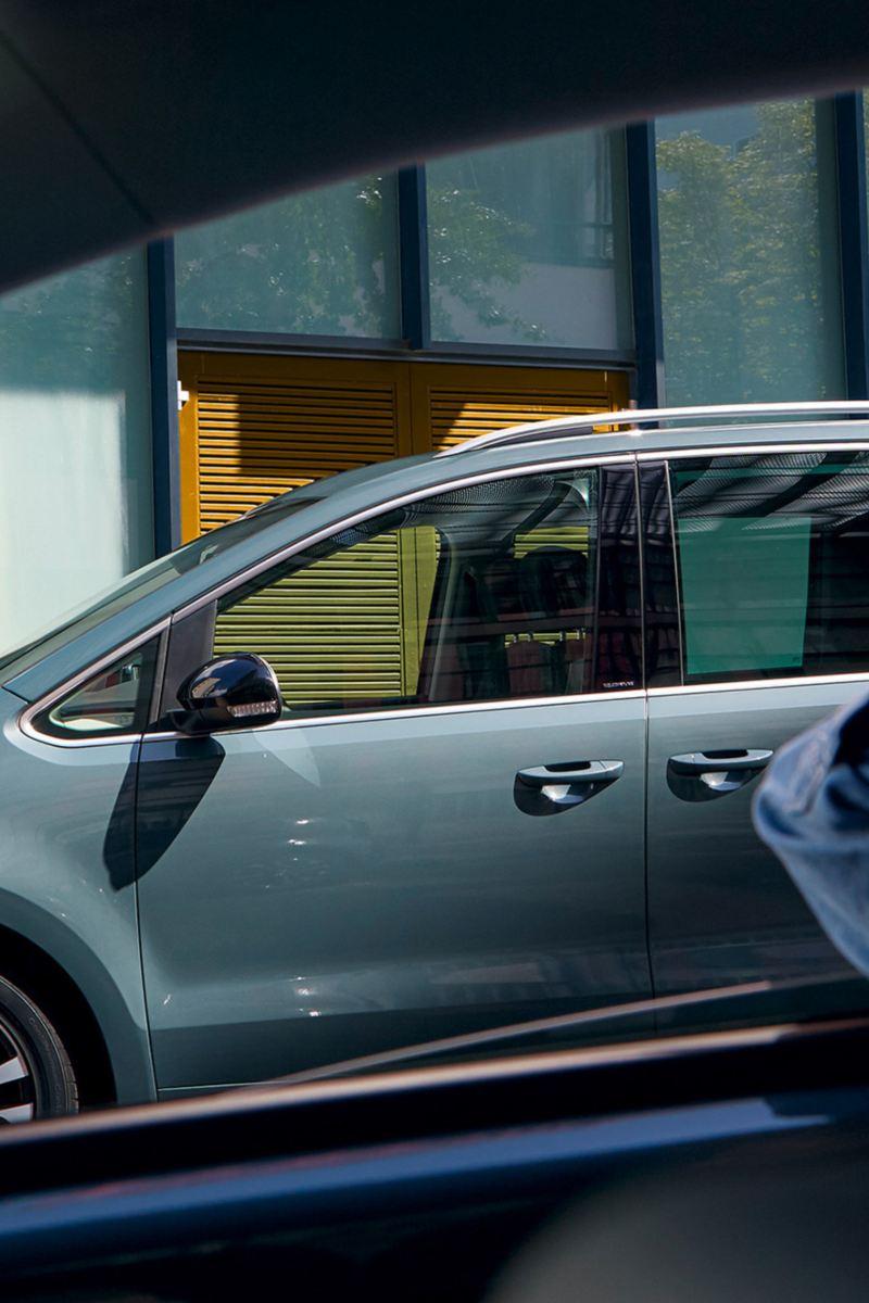 Une femme s'appuie à la fenêtre de la porte du passager avant, un Sharan IQ.DRIVE passe.