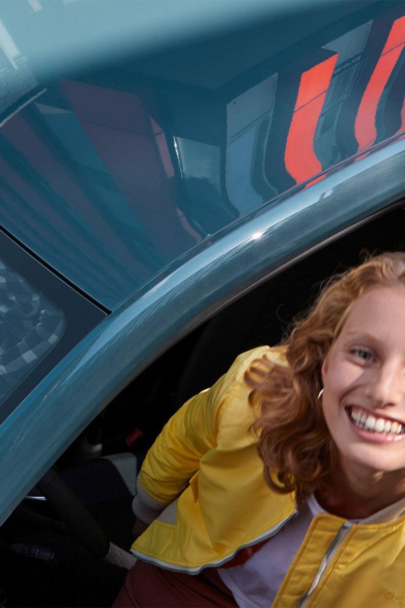 Frau schaut aus Fahrertür des up! IQ.DRIVE