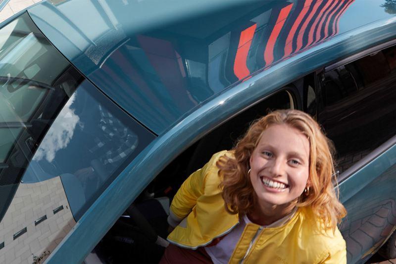 Vrouw kijkt uit het raam van de bestuurdersdeur van de up! IQ.DRIVE