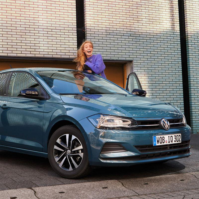 Lachende jonge vrouw leunt tegen de bestuurdersdeur van een Polo IQ.DRIVE