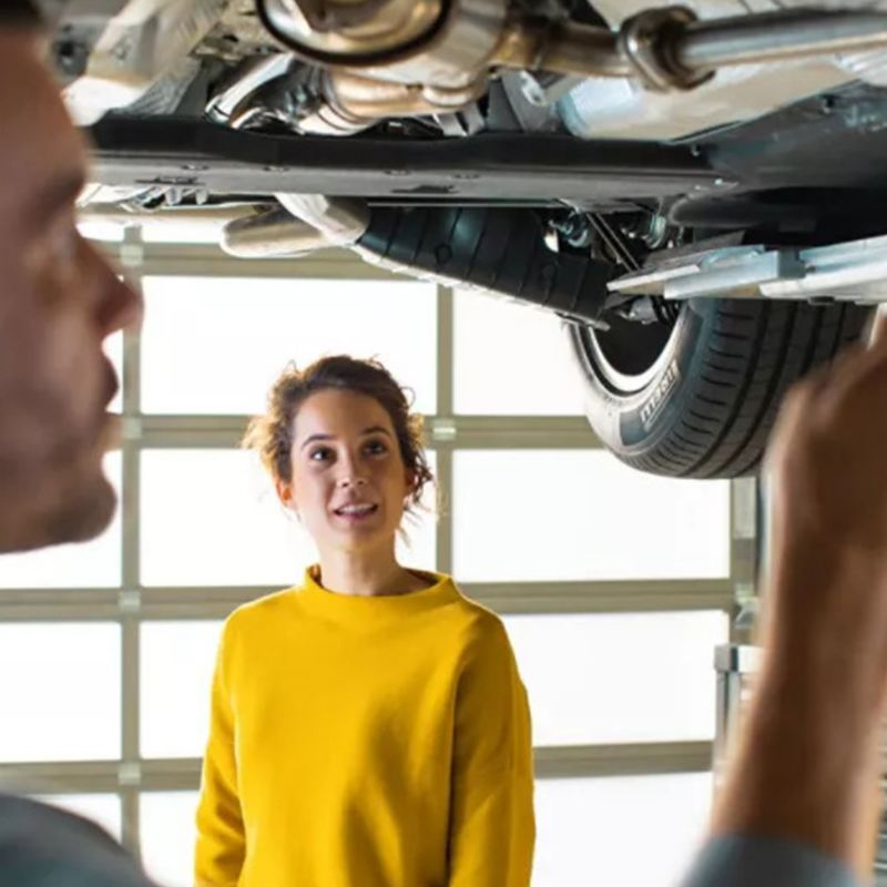 A woman is watching a car maintenance