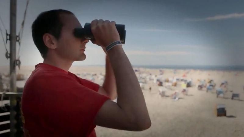 Ein Seenotretter sieht durch sein Fernglas.