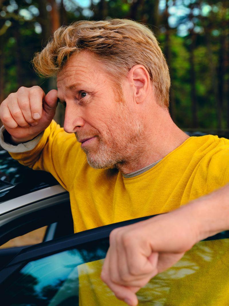Ein Mann steht in der halboffenen Fahrertür des ID.3 im Wald