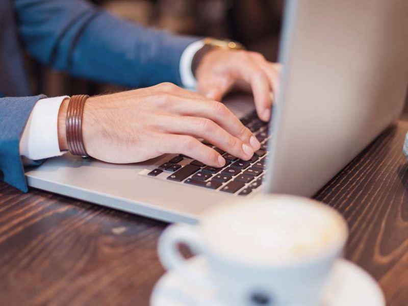 mani uomo digita su laptop