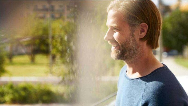 støtteordninger fra enova og andre insentiver ved kjøpe el varebil - blond mann med skjegg ser ut av vindu med vannspreder i bakgrunn