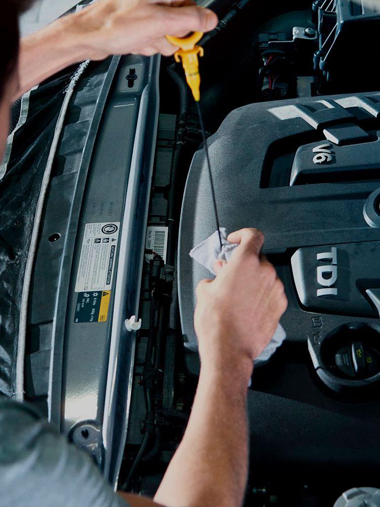 Um mecânico verifica o nível de óleo num veículo.