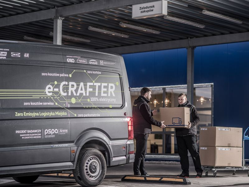 Kurierzy pakują paczki do Craftera oklejonego w logo Misja Zerowa Emisja