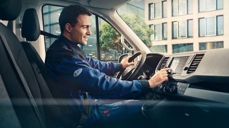 Um homem utiliza o sistema de navegação VW numa carrinha furgão imobilizada.