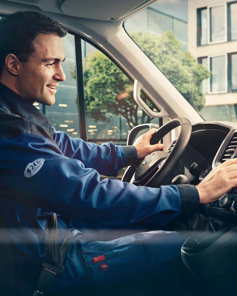 Man sitter i VW Transportbil och ställer in sitt navigationssystem