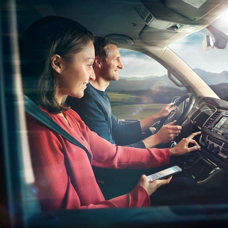 Duas pessoas no cockpit de uma carrinha furgão VW em movimento.