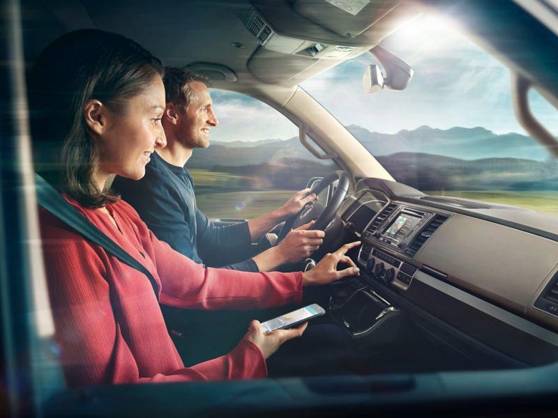 Duas pessoas no cockpit de uma carrinha furgão Volkswagen em movimento.
