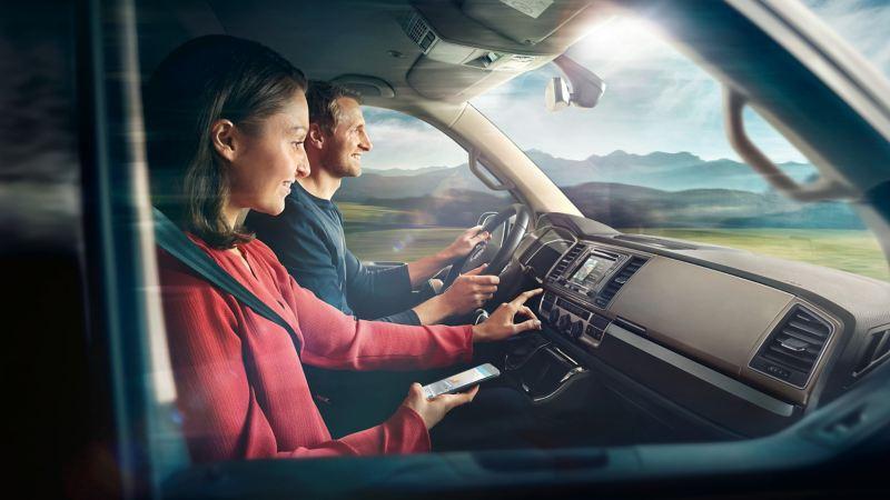 Un homme et une femme dans l'habitacle d'un véhicule en mouvement.