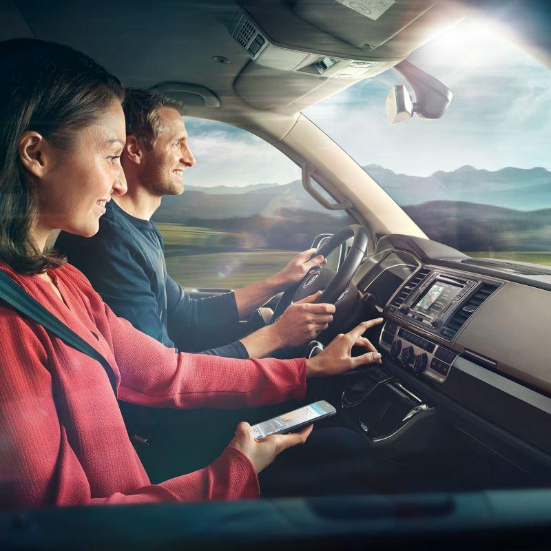 Ein Mann und eine Frau im Cockpit eines fahrenden Fahrzeugs.