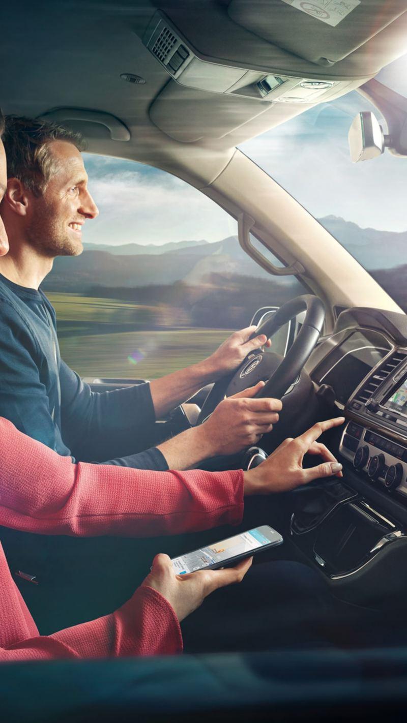 Um homem e uma mulher no cockpit de uma carrinha comercial Volkswagen.