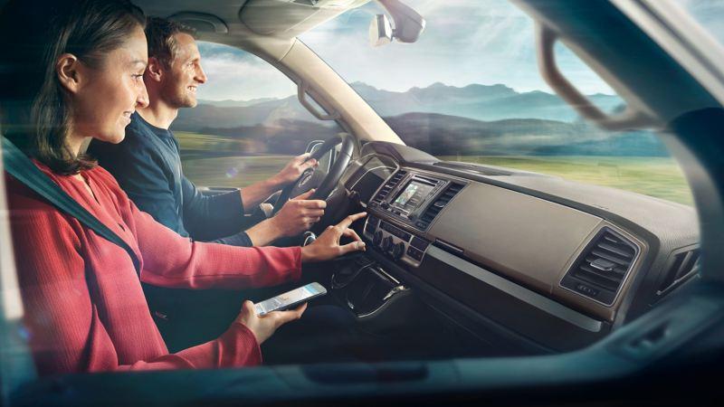 Par kör i en VW och håller i en mobiltelefon