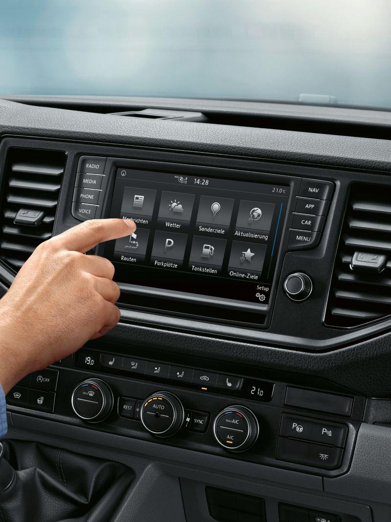 Crafter-umpipakettiauton ohjaamo. Taustalla näkyy monitoiminäytöllä Car-Net online-palvelu. Mies käyttää etualalla älypuhelintaan.