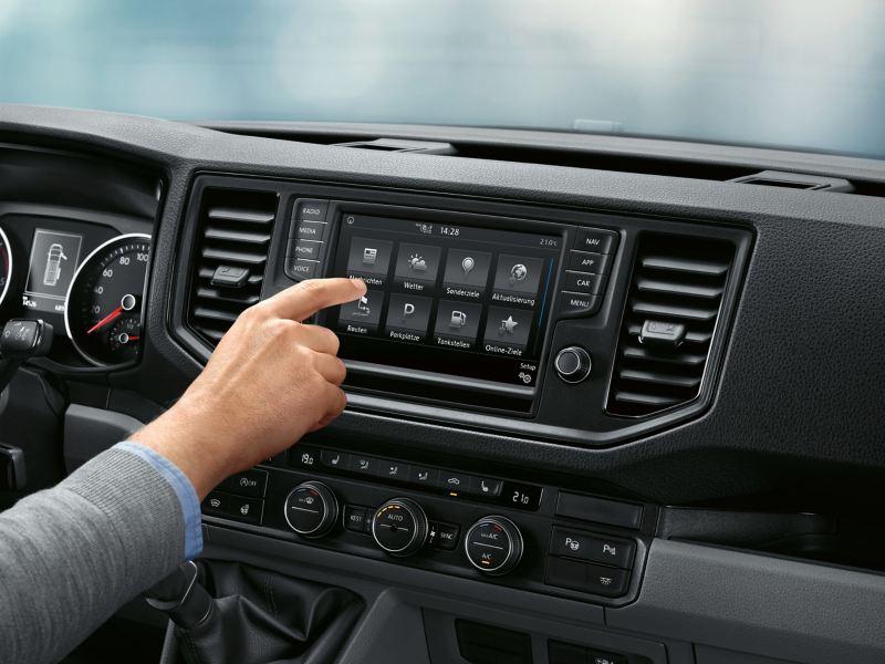 W kabinie zaparkowanego Craftera Furgon. Usługa Car-Net online jest widoczna w tle na wyświetlaczu wielofunkcyjnym. Mężczyzna na pierwszym planie obsługuje swój smartfon.