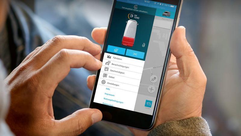 Zwei Hände halten ein Smartphone, auf dem eine App für Flottenmanagement läuft.