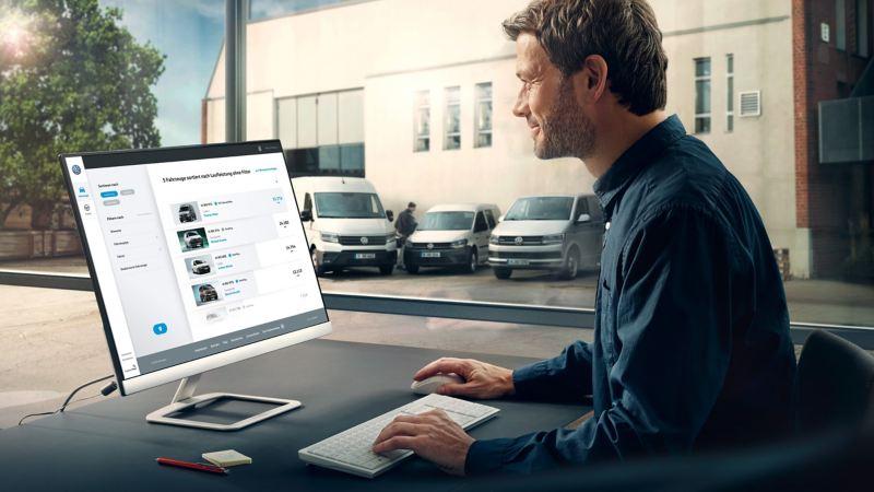 Man sitter framför en dator med VW transportbilar i bakgrunden