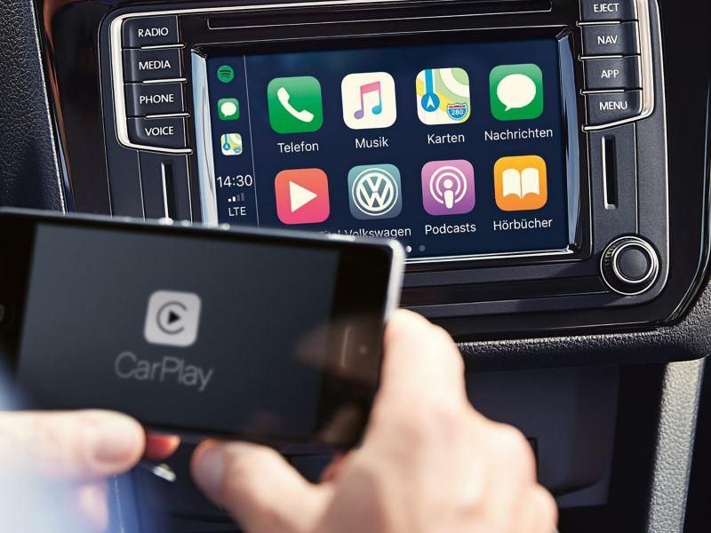 Vemos uma pessoa a aceder ao CarPlay no smartphone ligado ao veículo Volkswagen.