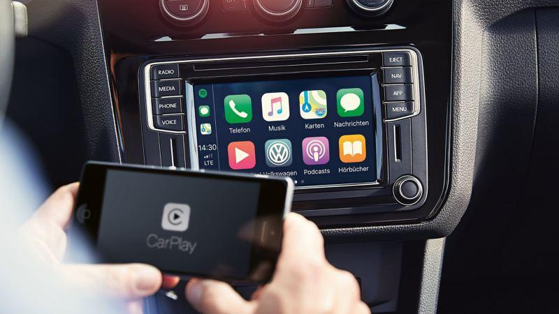 Zwei Hände halten ein Smartphone mit CarPlay-Symbol auf dem Display, im Hintergrund ist ein Infotainment-System zu sehen.