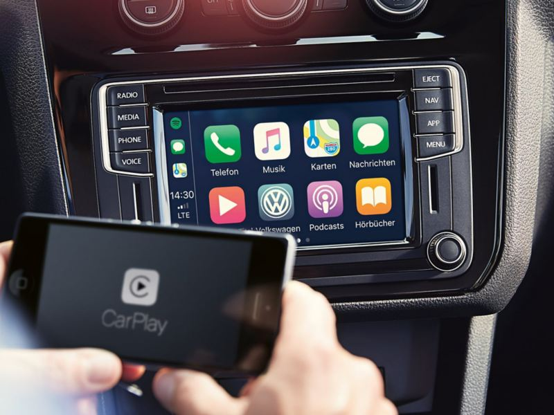 Two hands hold a smartphone with a CarPlay icon on the display; an Infotainment system is visible in the background.