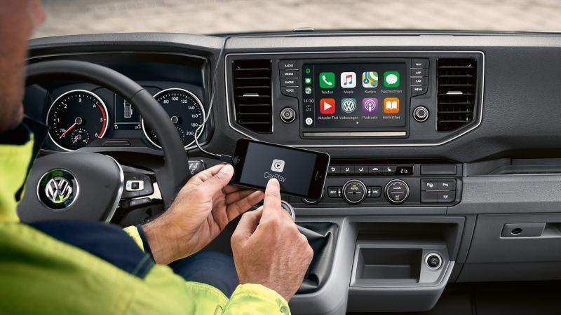 Eine Hand bedient das Radio- und Navigationssystem in der Fahrerkabine des Crafter Fahrgestell.