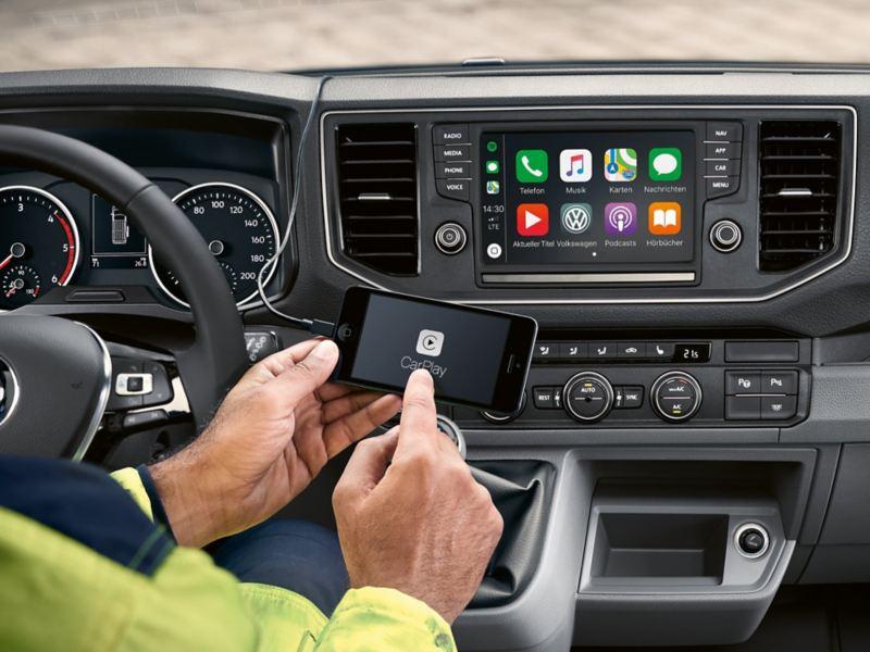 In de bestuurderscabine van de Volkswagen Crafter Bestelwagen. Op de achtergrond is de online dienst Car-Net op het multifunctionele scherm te zien. Op de voorgrond bedient een man zijn smartphone.