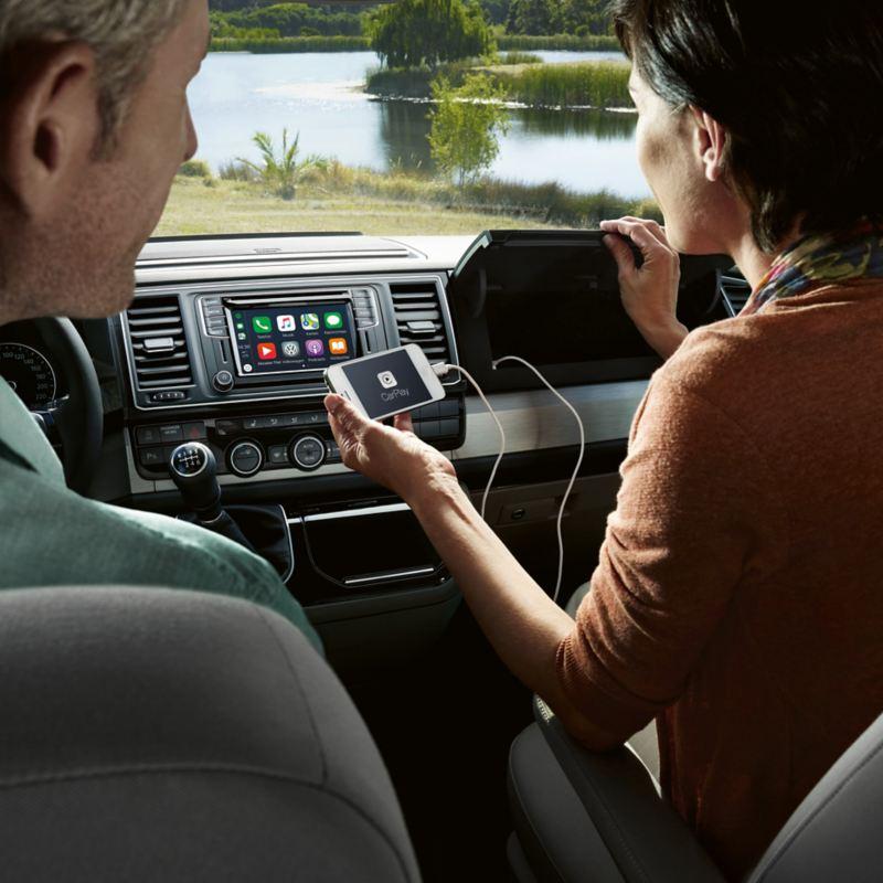 Uma mulher liga um smartphone a uma porta USB no porta-luvas de uma carrinha Volkswagen.