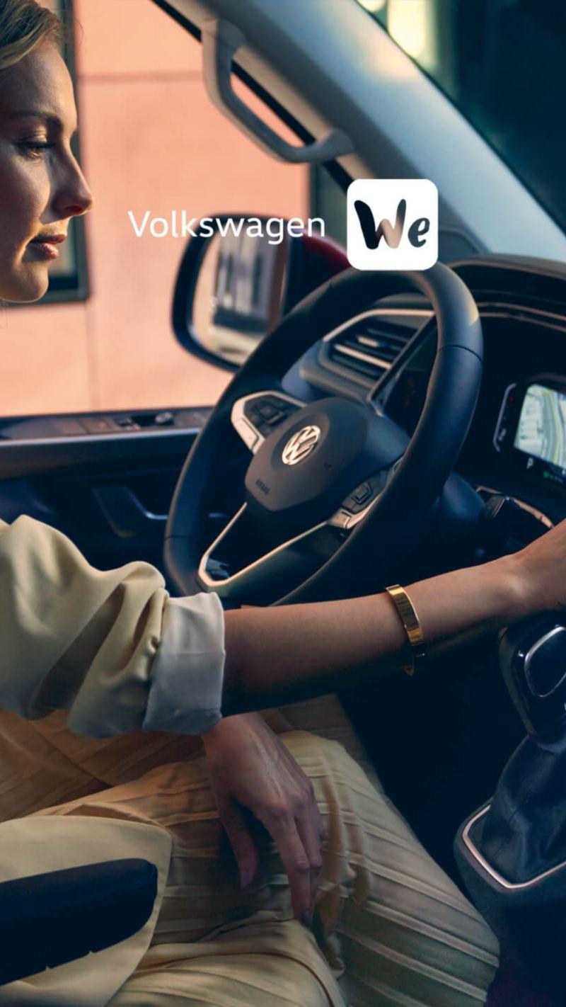 Uma mulher acede a uma aplicação digital através do cockpit digital da sua carrinha Volkswagen.