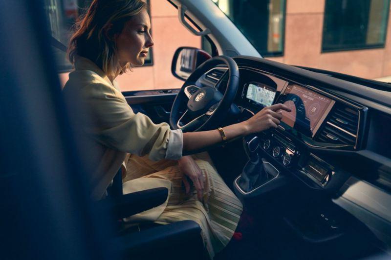 vw Volkswagen Multivan 6.1 Highline 7-seter familiebil minivan maxitaxi persontransport førerhus interiør førersete dame skrur på radio digital cockpit navigasjon gps multifunksjonsratt We Connect