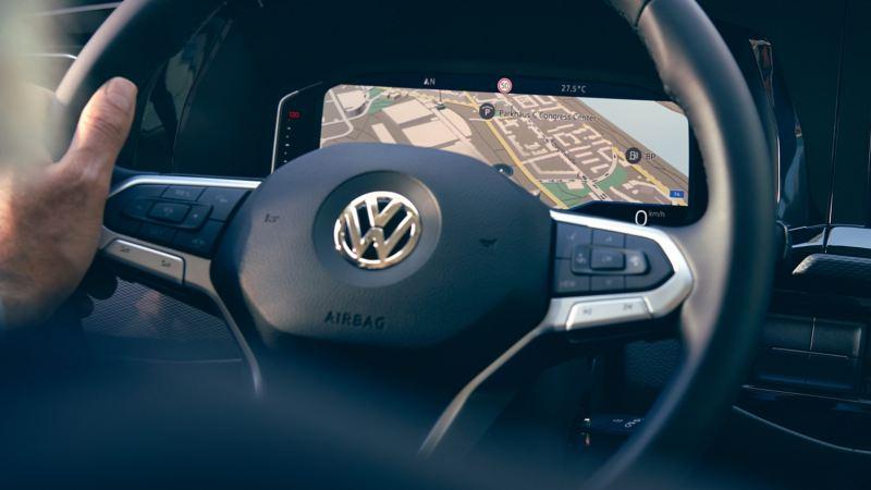 Eén hand aan het stuur, op het display is de kaart van een navigatiesysteem te zien.