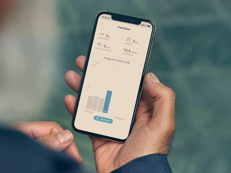 Eine Hand hält ein Smartphone auf dem die We Connect App für die Fahrdaten geöffnet ist.