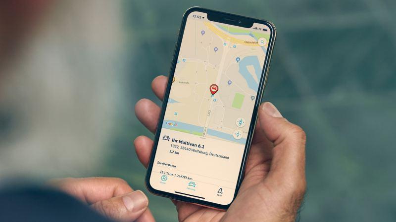 Auf dem Display eines Handys wird die Parkposition des Multivan 6.1 angezeigt.