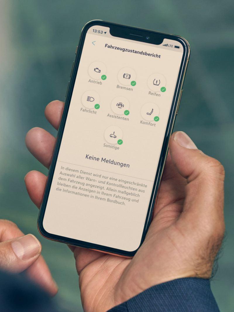 Eine Hand hält ein Smartphone auf dem die We Connect App für den Fahrzeugzustandsbericht geöffnet ist.