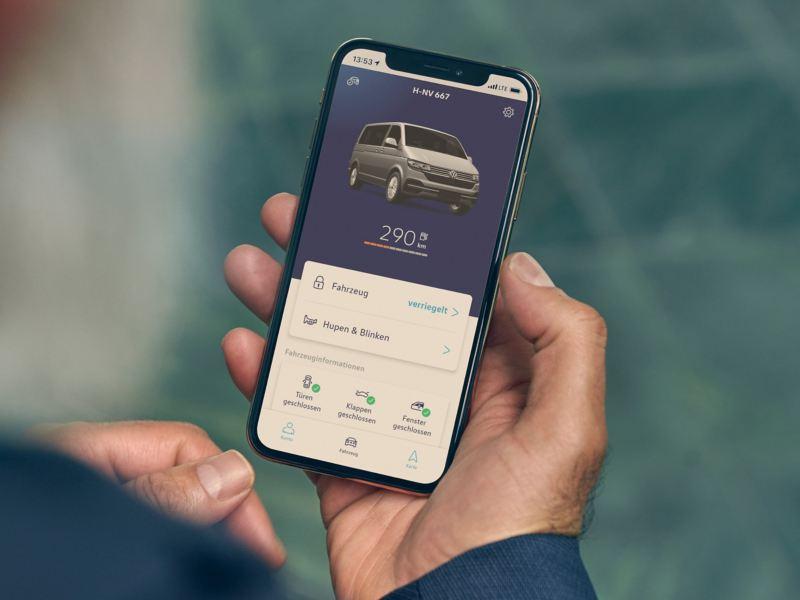 Eine Hand hält ein Smartphone auf dem die We Connect App für den Fahrzeugstatus geöffnet ist.