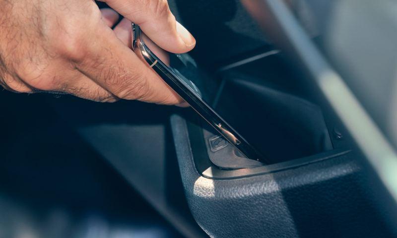 Ein Smartphone wird in der induktiven Ladestation eines Multivan 6.1 aufgeladen.