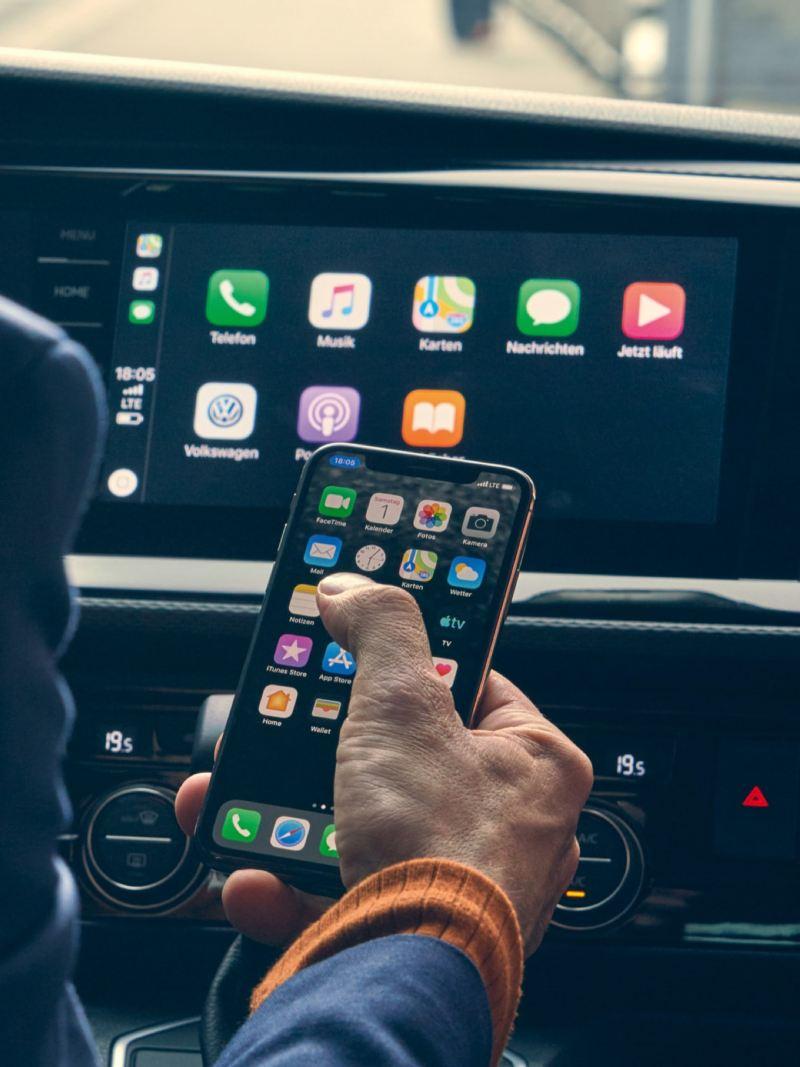 Vista para o visor do cockpit e uma mão que opera a aplicação We Connect da Volkswagen.