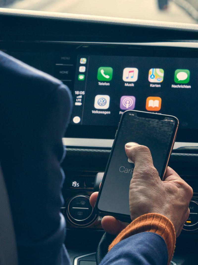 Sguardo sul display della plancia e una mano che utilizza l'app Connect